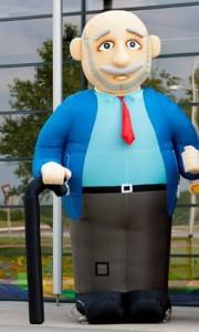Deze afbeelding laat zien een opblaasbare abraham met wandelstok. Abraham heeft een blauw jasje met rode stropdas. Een snor en een klein ringbaardje.