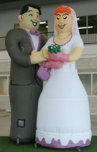 Deze afbeelding toont een bruidspaar. De man in een lichtgrijs pak met rose vlinderdas, de bruid in een mooie witte jurk met roze handschoenen en bruidsboeket. De bruid draagt een witte sluier naar achter toe. Beide houden elkaar vast.