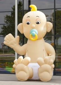 Zwaaiende baby in luier, 3 meter 80 hoog met gele kuif en speen in de mond. De baby zit op zijn billen.